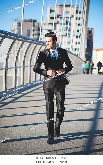 Young businessman crossing bridge