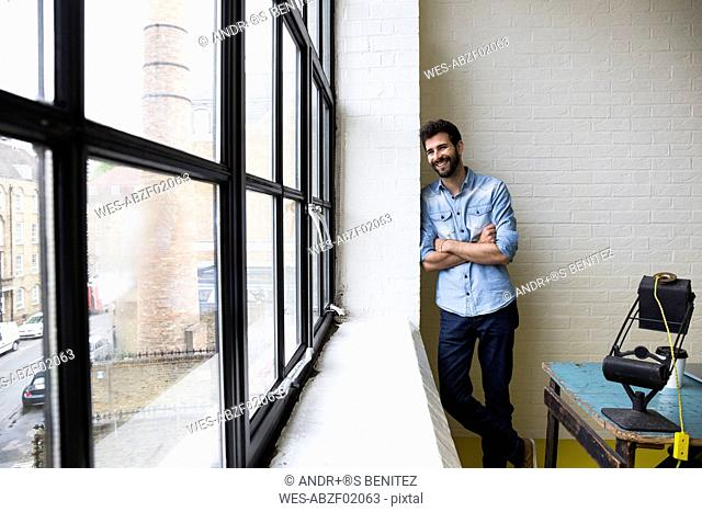 Smiling man leaning against a wall in his loft