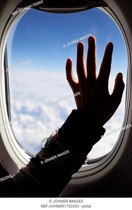 Human hand against plane window