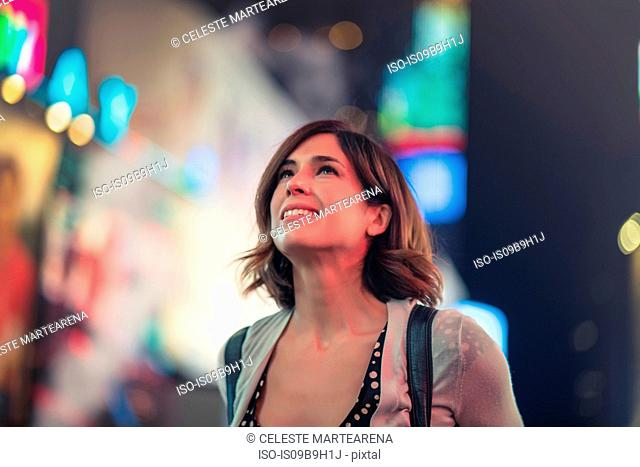 Portrait of woman in Times Square looking up, New York, United States, North America