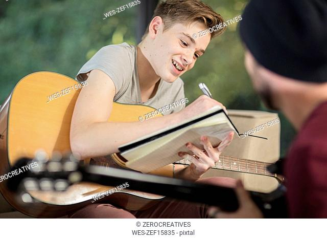 Musician teaching student how to play guitar