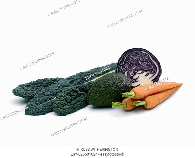 a selection of fresh healthy vegetables on a white background including Kale,red cabbagel, Avocado and Carrotts