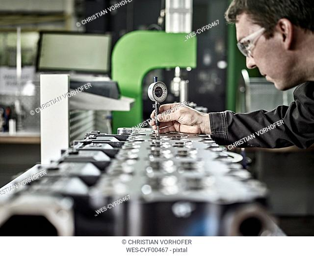 Worker in metalworking factory controlling cylinder head
