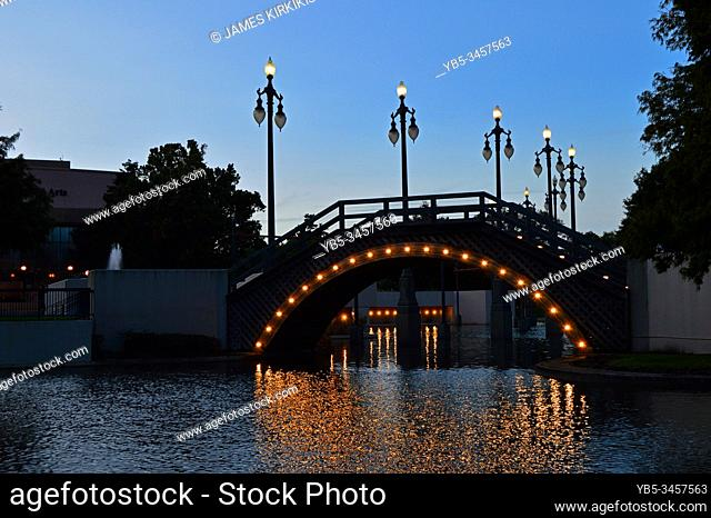 A lighted arched bridge carries pedestrians over a lake in Armstrong Park in New Orleans