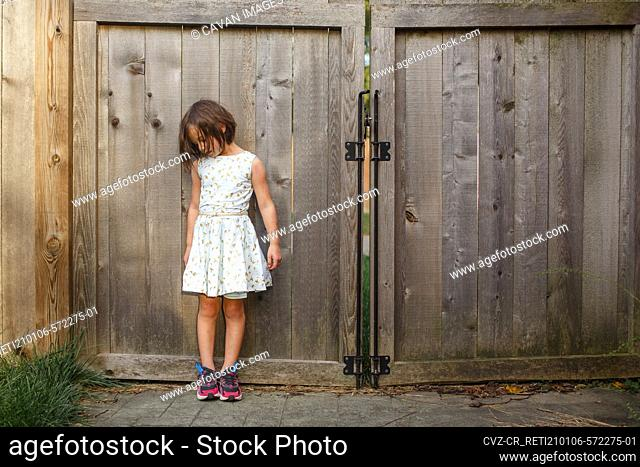 A little girl in beautiful dress leans on wooden gate looking down