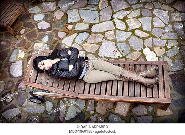Woman lying on a chaise longue. February 2014, Italy