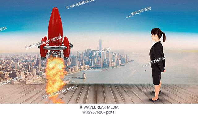 Digital composite image of businesswoman standing on pier and watching rocket launch against city