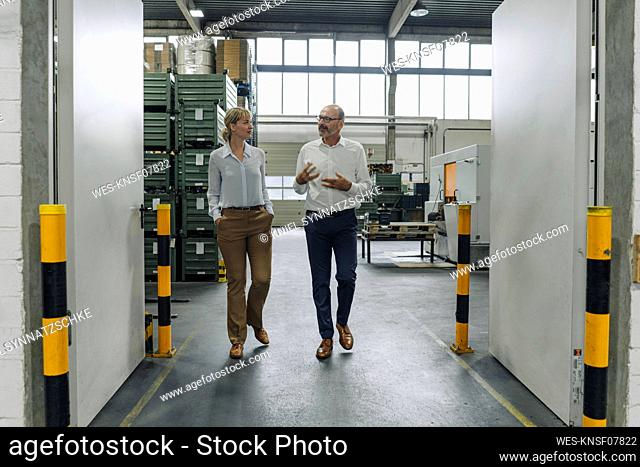 Man and woman walking and talking in a factory
