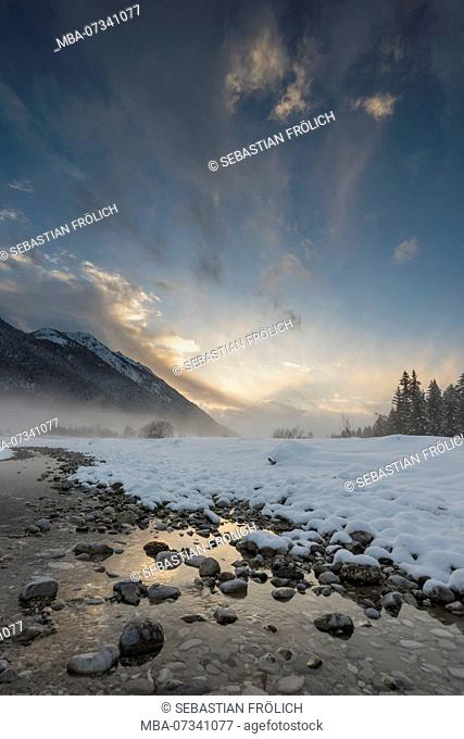An almost parched branch of the Isar river in wintertime, sundown, snow
