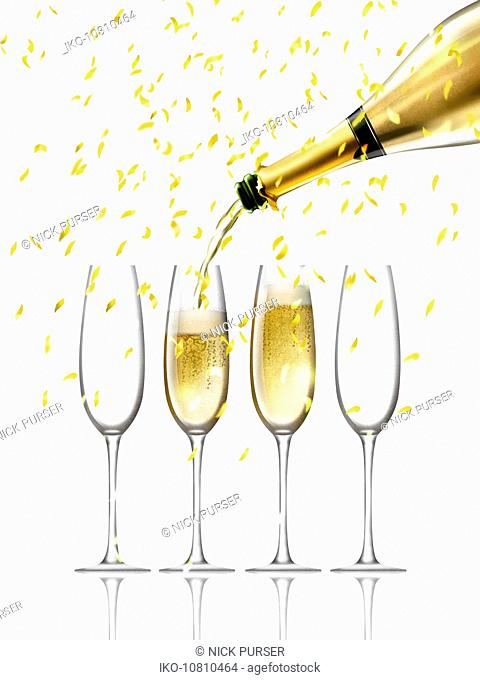 Confetti falling on gold champagne bottle filling four champagne flutes