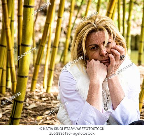 Melancholic blond woman sitting in the middle of bamboos. She is dressed in white, has sunglasses on and looks sad, depressed