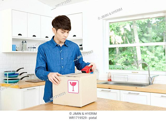 A man packing moving boxes in a kitchen
