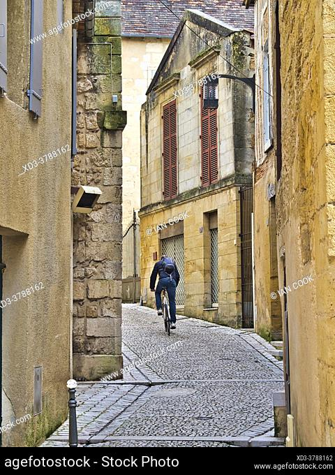 man riding bicycle on a narrow street, Bergerac, Dordogne Department, Nouvelle-Aquitaine, France