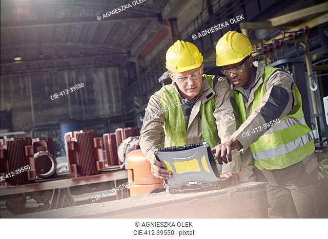Steelworkers using laptop in steel mill