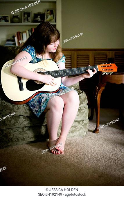 Picture of teenage girl (13-15) playing acoustic guitar at home