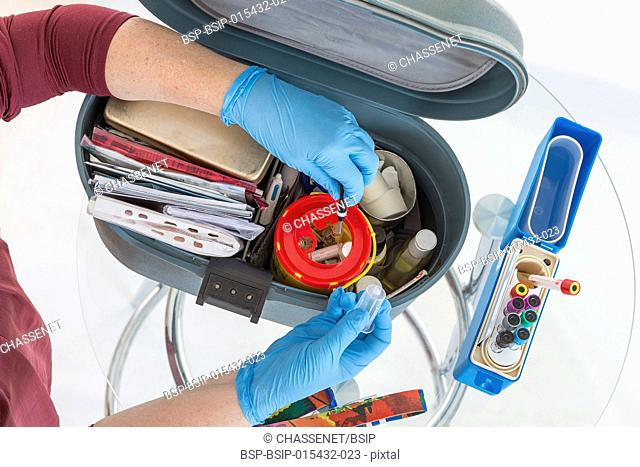 Nurse organising her First aid briefcase medical tools . Assistance equipment on white