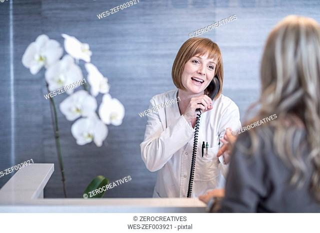 Receptionist greeting patient while on the phone