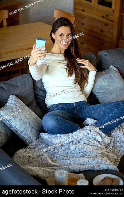 beautiful young smiling woman in white sweater taking selfie on smartphone on gray sofa