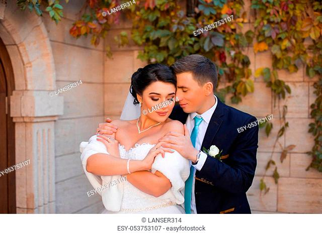 The groom put his hands on the bride's shoulders