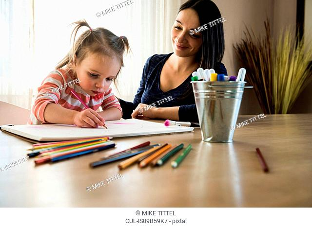 Female toddler at table with mother drawing in sketchbook