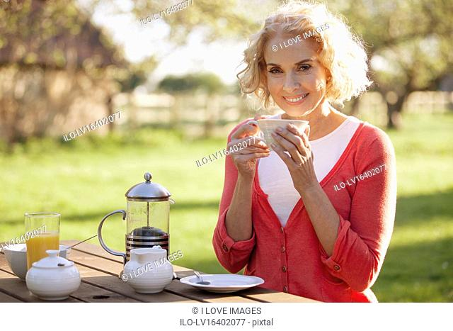 A mature woman sitting at a garden bench drinking coffee