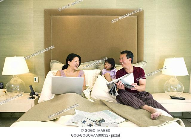 Parents with daughter 4-5 sitting on bed, smiling