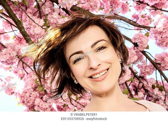 Young joyful caucasian brunette posing with flowering sakura tree. Beauty and nature