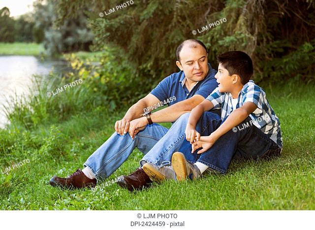 Father and son spending quality time together in a park; Edmonton, Alberta, Canada