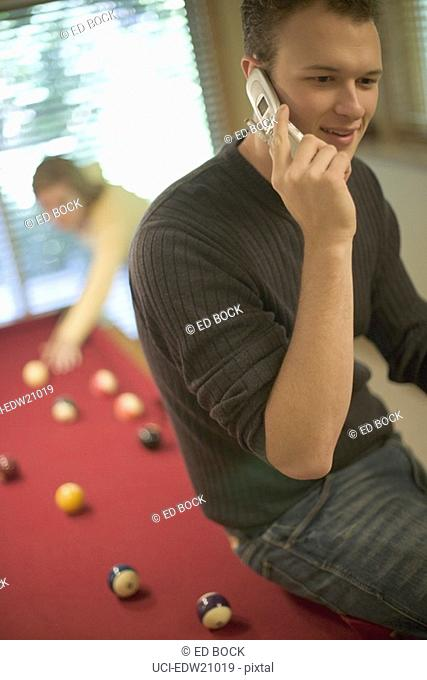 Man talking on cell phone sitting on pool table