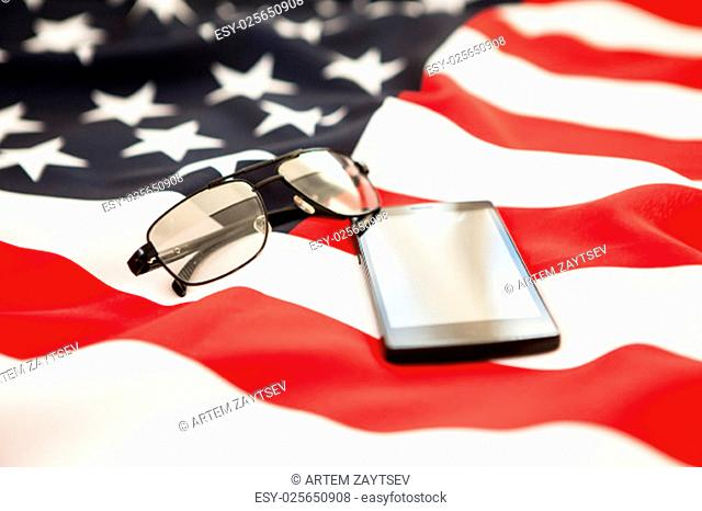 Black smartphone and sunglasses lying on the background of the flag of the United States