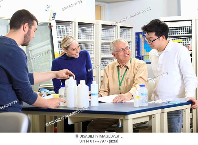 Engineering professor discussing learning objectives with students in a chemical laboratory