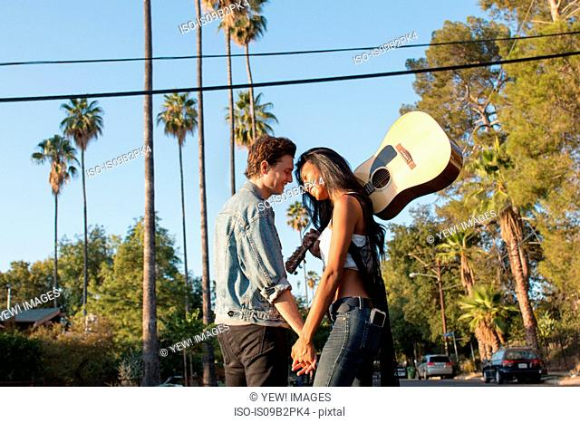 Young couple outdoors, face to face, laughing, young woman holding guitar