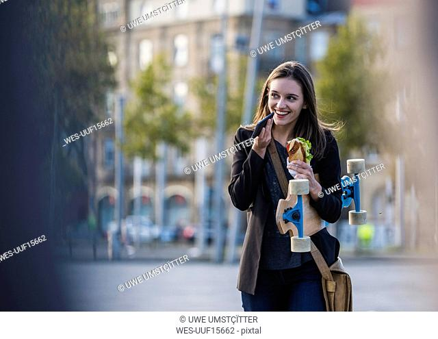 Smiling young woman with longboard and snack in the city using cell phone