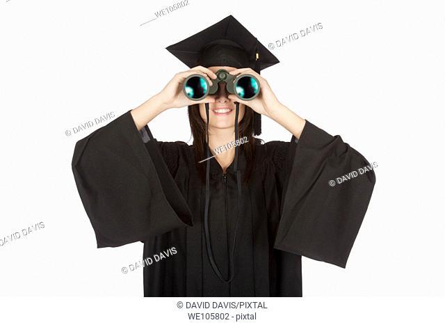 Beautiful Caucasian woman wearing in a black graduation gown and looking through binoculars