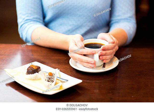 drinks, people and lifestyle concept - close up of woman hands holding cup with hot black coffee and dessert