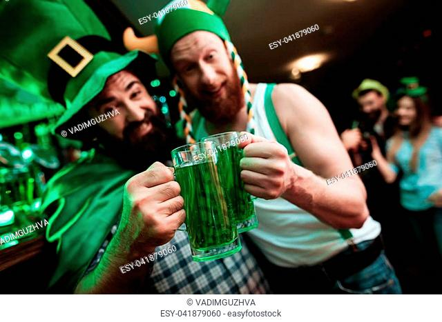 Two men are drinking beer in a bar. He celebrates St. Patrick's Day with friends