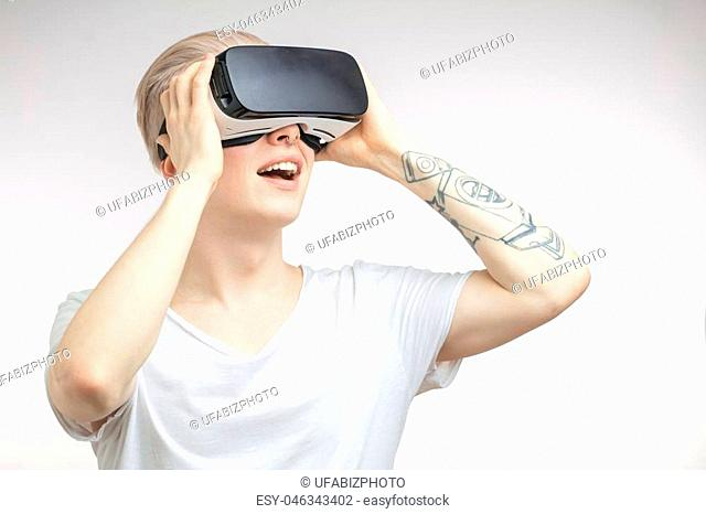 Blonde young student man putting VR goggles on head, experiencing virtual reality using 3d headset. Technology, science, innovation and cyberspace concept
