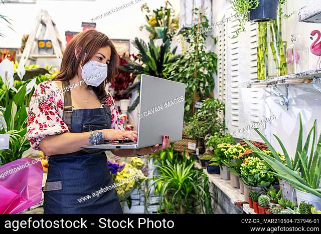 enterprising woman taking inventory with her laptop