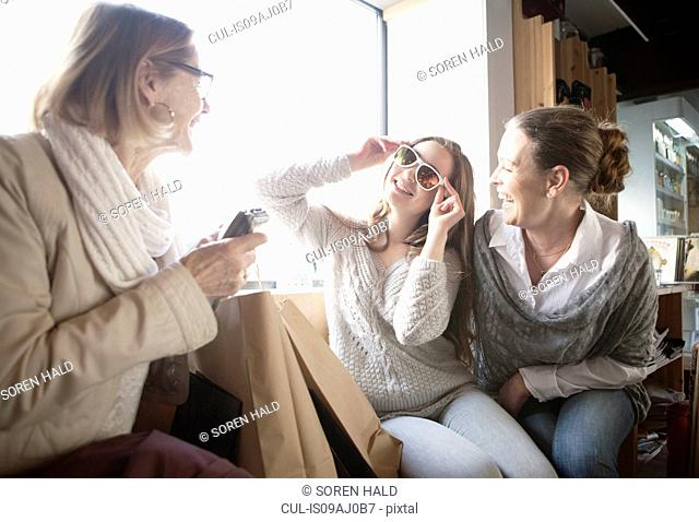 Three generation females trying on sunglasses in shop