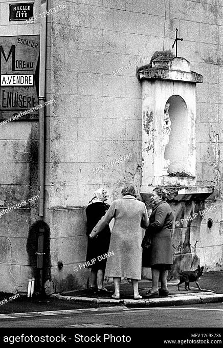 Three old ladies and a dog chat on the corner of Rue de la Cite in Cergy Pontoise, northern France 1994