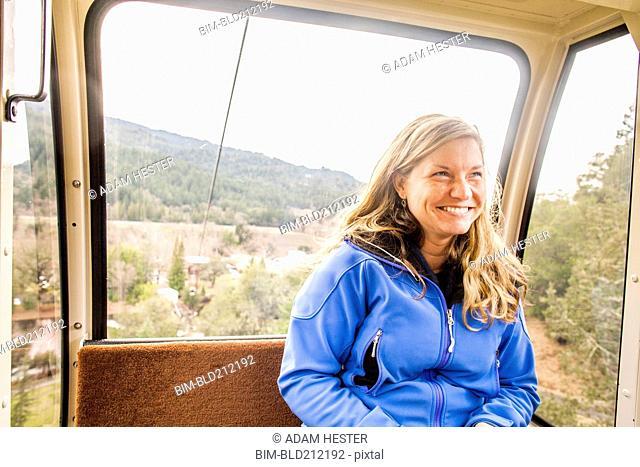 Caucasian woman riding in aerial tram