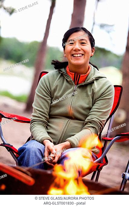 A smiling Japanese American women sits in a camp chair next to a campfire while roasting a hotdog