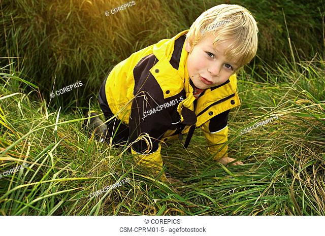 Young child crawling out of a ditch on his hands and knees