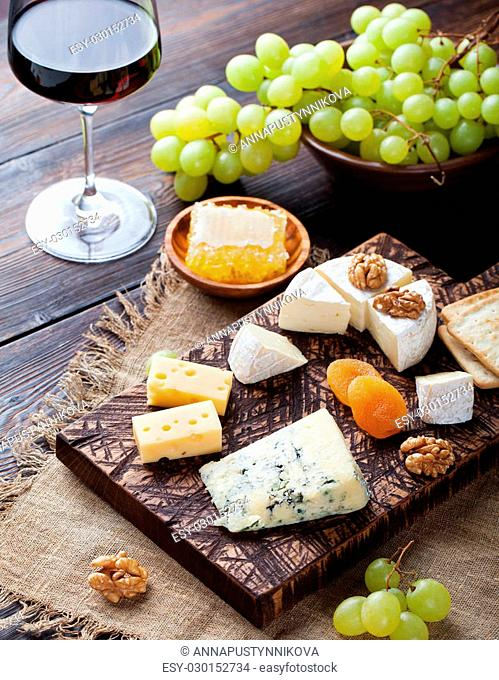 Red wine in glass with cheese, honey, nuts and grape