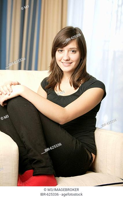 Girl (17) with red socks sitting on sofa, smiling