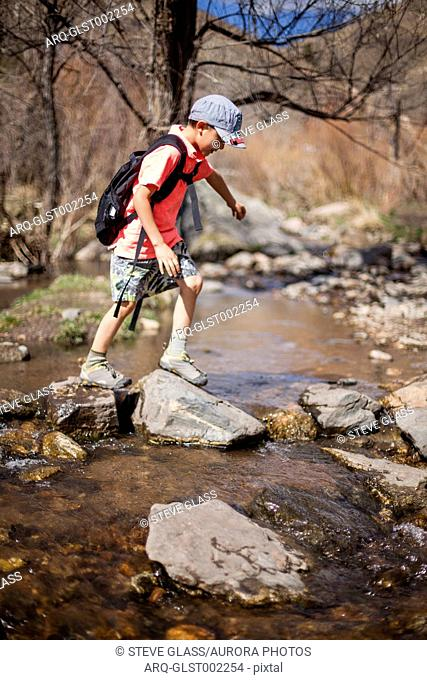 A 6 year old Japanese American boy crosses a stream while hiking along the Hewlett Gulch Trail, Colorado