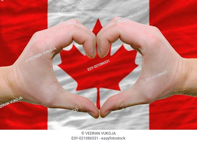 Heart and love gesture showed by hands over flag of canada backg