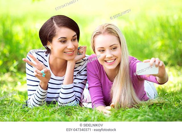 Nice looking young women outdoors. Women making selfie photo with mobile phone. Beautiful green park as a background