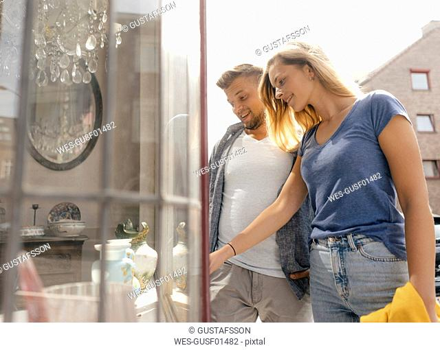 Belgium, Tongeren, happy young couple looking in shop window of an antique shop