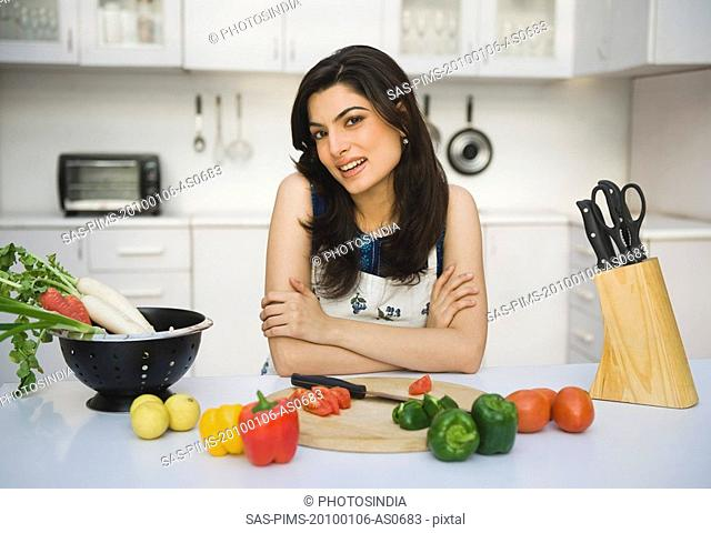 Portrait of a woman leaning on a kitchen counter